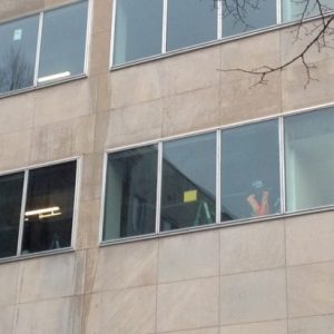 Construction workers now in the windows where famed columnists used to work
